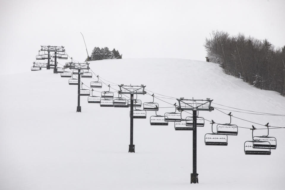 Idle chairlifts are seen on the shut-down slopes of Blue Mountain Ski Resort in The Blue Mountains, Ontario, on the first day of a provincial lockdown amid a 12-day trend of over 2,000 daily COVID-19 cases, Saturday, Dec. 26, 2020. (Cole Burston/The Canadian Press via AP)
