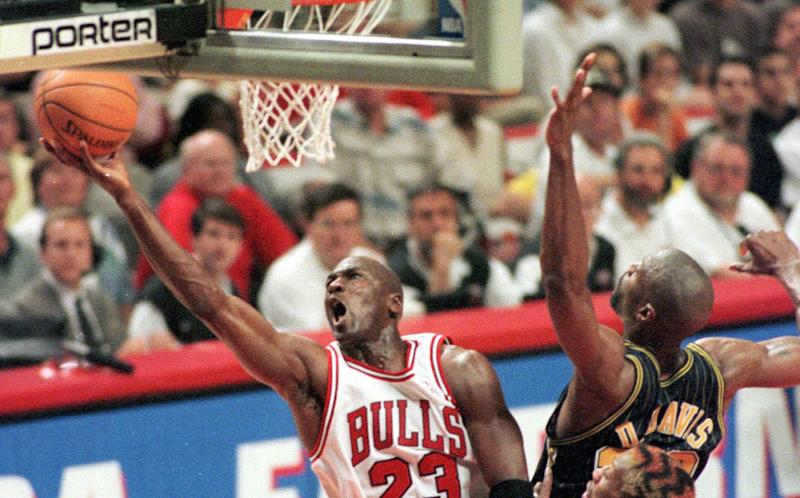 Chicago Bulls' Michael Jordan drives for the score past Indiana Pacers' Dale Davis (32) during the second quarter of Game 7 of the Eastern Conference Finals Sunday, May 31, 1998, in Chicago. Jordan became the NBA's all-time leading playoff scorer during the first half. His 5,758 points trailed Kareem Abdul-Jabbar by 5 at the start of the game and he scored 15 in the first half. (AP Photo/Mike Fisher)