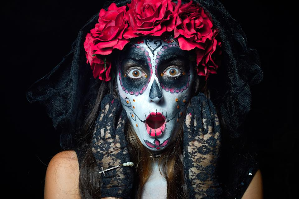 Portrait of woman dressed as catrina, skull to honor the dead in Mexico. Dressed with white face, black eyes and a bouquet and wreath of red roses. black background and light rembrandt.