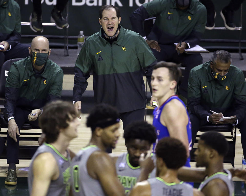 """File-Baylor head coach Scott Drew, top center, reacts to a play in the second half of an NCAA college basketball game against Kansas, Monday, Jan. 18, 2021, in Waco, Texas. """"You get to spend the entire year helping your game get better without the outside pressure or having to worry about being ready for each and every game, so it's truly one year of development,"""" Drew said of redshirts, for current players and Bears in the past decade who went on to play professionally. (AP Photo/Jerry Larson, File)"""