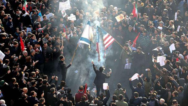 PHOTO: Iranians set a U.S. and an Israeli flag on fire during a funeral procession for Qassem Soleimani and other victims of a U.S. drone strike, in the capital Tehran on Jan. 6, 2020. (Atta Kenare/AFP via Getty Images)