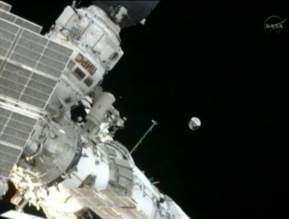 Expedition 32 commander Gennady Padalka, a Russian cosmonaut, throws the small Spherical Satellite into orbit during an Aug. 20, 2012, spacewalk outside the International Space Station. The small satellite will spend three months in orbit and b
