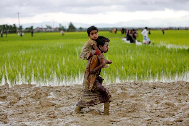 <p>A Rohingya boy carries a child while walking in the mud after crossing the Bangladesh-Myanmar border in Teknaf, Bangladesh, Sept. 1, 2017. (Photo: Mohammad Ponir Hossain/Reuters) </p>