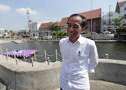 Indonesian President Joko Widodo smiles as he talks to The Associated Press during his visit at the newly-revitalized 18th century Kali Besar Canal at the Old Town in Jakarta, Indonesia, Friday, July 26, 2019. Widodo says he is freed from political constraints in his final term and vows to push sweeping economic reforms. (AP Photo/Dita Alangkara)