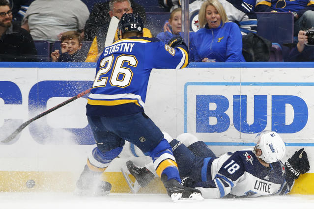St. Louis Blues' Paul Stastny, left, checks Winnipeg Jets' Bryan Little off the puck during the first period of an NHL hockey game Friday, Feb. 23, 2018, in St. Louis. (AP Photo/Billy Hurst)