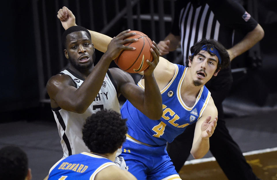 Oregon forward Eugene Omoruyi (2) hauls in a rebound next to UCLA guard Jaime Jaquez Jr. (4) during the first half of an NCAA college basketball game Wednesday, March 3, 2021, in Eugene, Ore. (AP Photo/Andy Nelson)