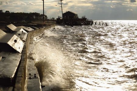 Waves pound the seawall near a crab house on Saxis Island in Virginia October 25, 2013. REUTERS/Kevin Lamarque