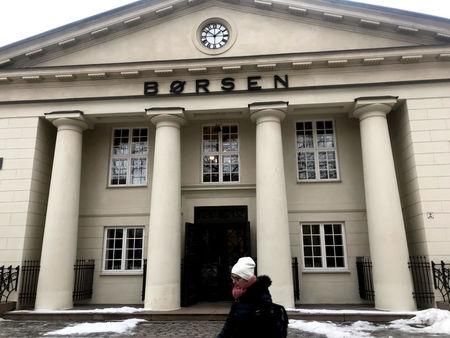 FILE PHOTO: A woman walks past the Oslo Stock Exchange building in Oslo