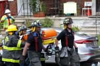 Fire fighters transport an injured person on a stretcher at the scene of an explosion in a residential area of Baltimore