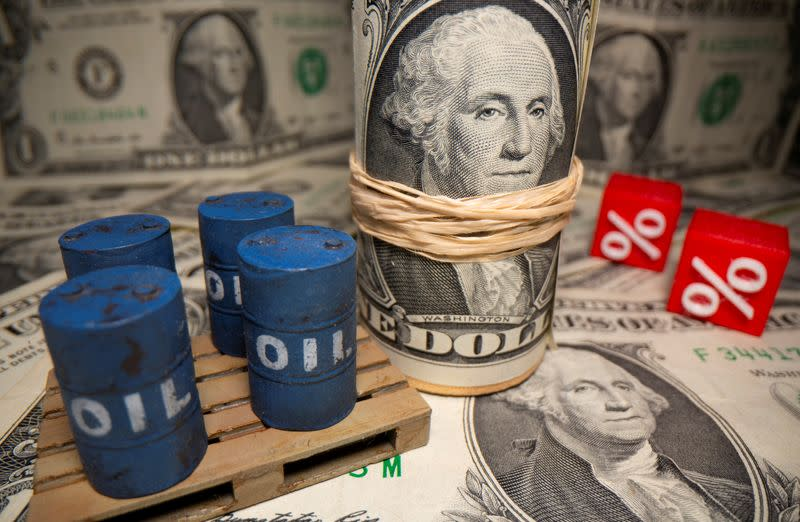 FILE PHOTO: 3D printed oil barrels and percentage symbols are seen in front of dollar banknotes in this illustration