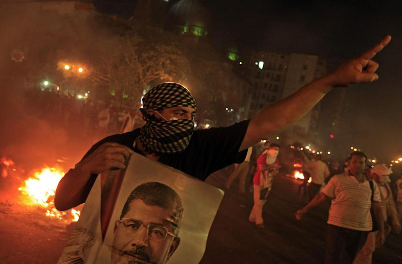 A Supporter of ousted President Mohammed Morsi holds a poster of him during clashes in downtown Cairo, Egypt, Monday, July 15, 2013. Thousands of supporters of deposed President Mohammed Morsi held mass rallies and marched in the streets Monday to demand his return to office. The protest turned violent in downtown Cairo as police fired tear gas at pro-Morsi protesters who burned tires, threw rocks and blocked traffic flow on a main roadway running through the heart of the capital. (AP Photo/Khalil Hamra)