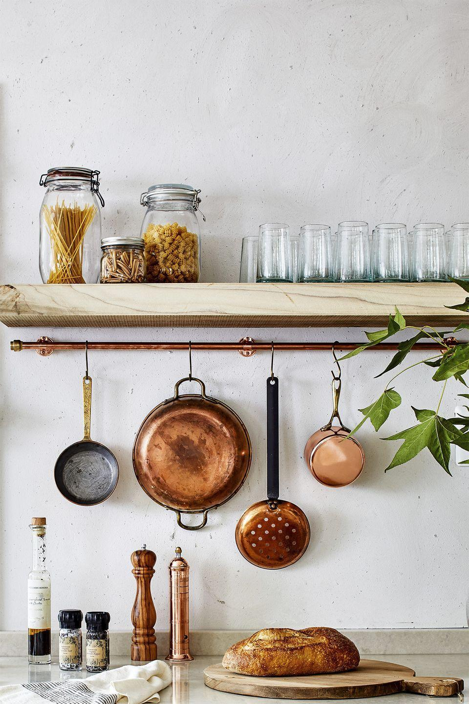 """<p>A piece of copper pipe from your local hardware store can create space for hanging pots, measuring cups and other kitchen essentials.</p><p><strong>RELATED: </strong><a href=""""https://www.goodhousekeeping.com/home/organizing/tips/g1397/small-kitchen-storage/"""" rel=""""nofollow noopener"""" target=""""_blank"""" data-ylk=""""slk:Storage Tricks for Small Kitchens"""" class=""""link rapid-noclick-resp"""">Storage Tricks for Small Kitchens</a></p>"""