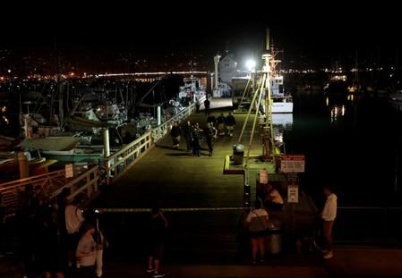 FILE PHOTO: Rescue personnel exit the city pier after unloading the victims of a pre-dawn fire that sank a commercial diving boat off the coast of  Santa Barbara, California