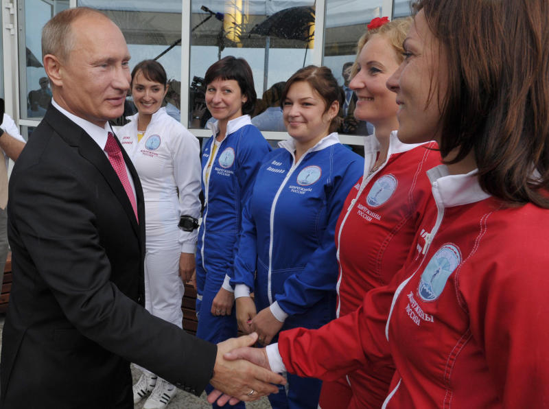 "Russian President Vladimir Putin, left, greets a group from the Russian Women's Parachute team ""Treasures of Russia"" as he attends the Russian air force's 100th anniversary in Zhukovsky, outside Moscow, Russia, on Saturday, Aug. 11, 2012. (AP Photo/RIA-Novosti, Alexei Nikolsky, Presidential Press Service)"
