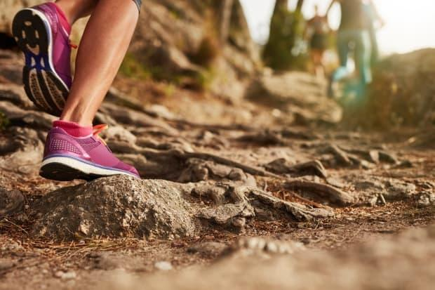 A close-up shot of an athlete wearing running shoes on a rocky trail. (Jacob Lund/Shutterstock - image credit)