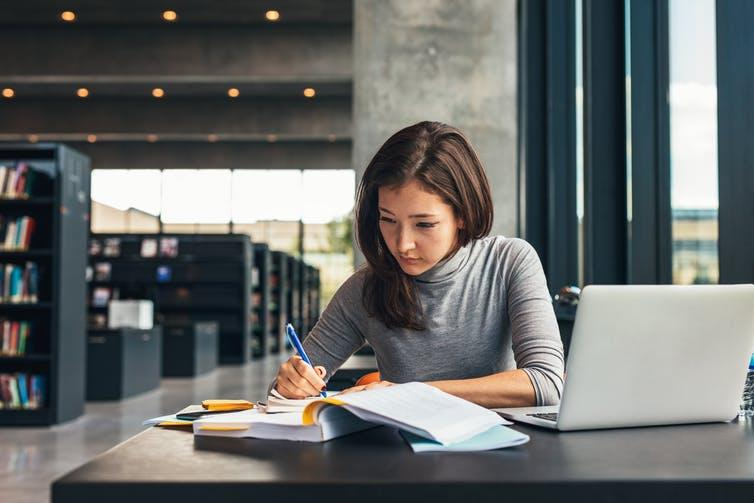 Woman taking notes from book in library