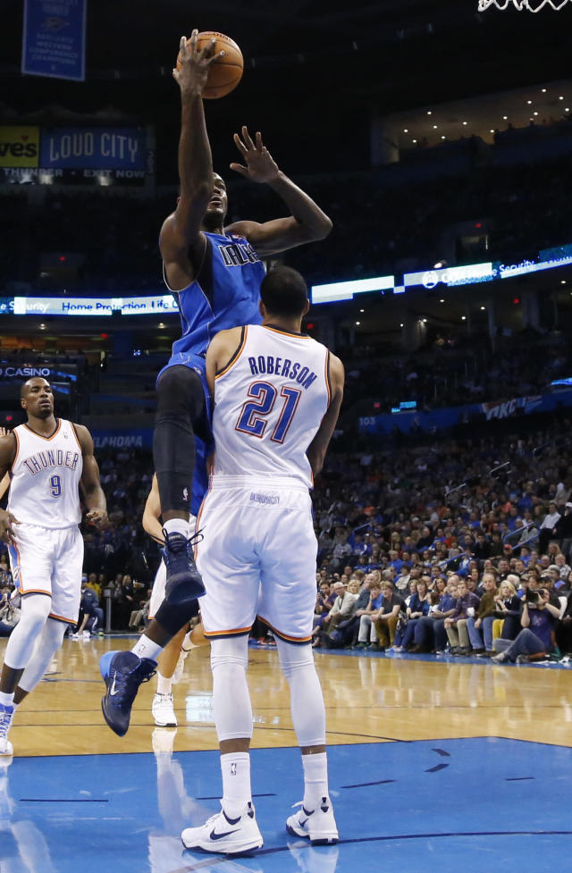 Dallas Mavericks center Samuel Dalembert (1) commits an offensive foul as he shoots over Oklahoma City Thunder forward Andre Roberson (21) in the first quarter of an NBA basketball game in Oklahoma City, Sunday, March 16, 2014. (AP Photo/Sue Ogrocki)