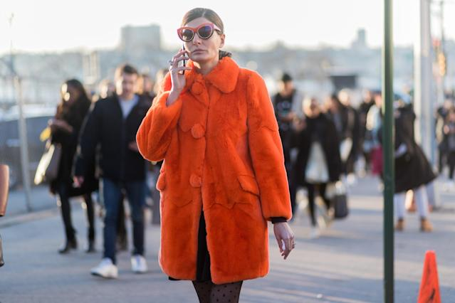 <p>If you prefer to wear fur during the winter, take a style cue from Giovanna Battaglia and opt for a bold colored faux version, accessorized with matching sunglasses. (Photo: Getty) </p>