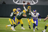 Green Bay Packers quarterback Aaron Rodgers (12) throws a pass while being chased by Los Angeles Rams' Aaron Donald (99) during the first half of an NFL divisional playoff football game Saturday, Jan. 16, 2021, in Green Bay, Wis. (AP Photo/Matt Ludtke)