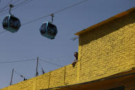 A man stands on a rooftop as cable cars overhead run between the Campos Revolucion and Tlalpexco stations, during the inauguration of a new aerial public transit system dubbed the Cablebus, in the Cuautepec neighborhood of northern Mexico City, Thursday, March 4, 2021. (AP Photo/Rebecca Blackwell)