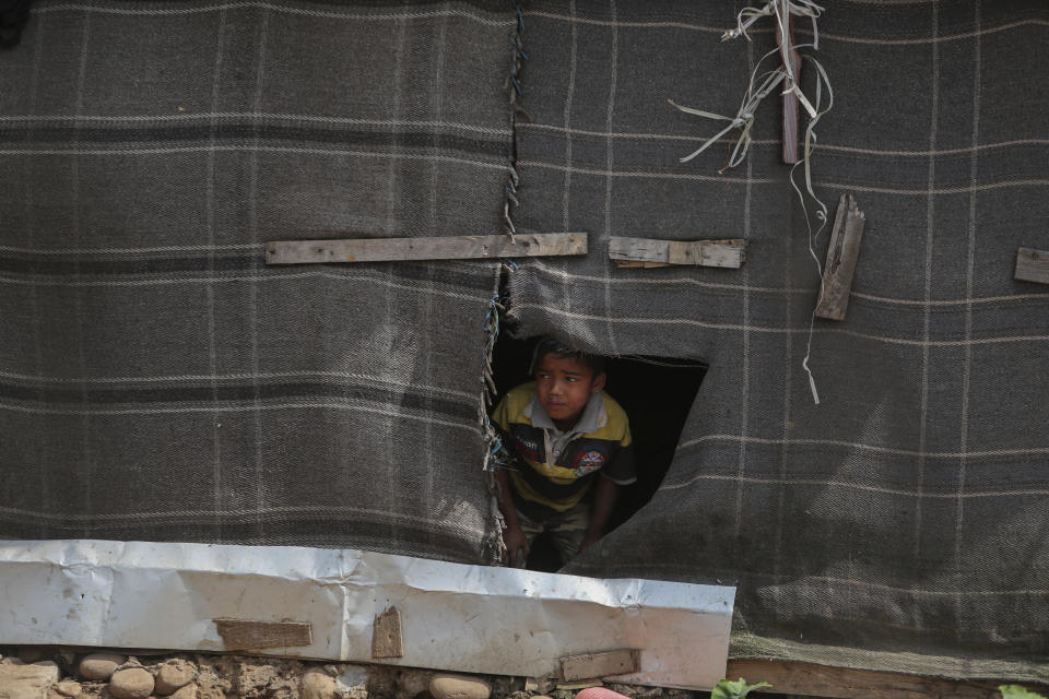 A Rohingya refugee boy looks through a torn blanket used as a partition at a makeshift camp on the outskirts of Jammu, India, Sunday, March 7, 2021. Authorities in Indian-controlled Kashmir have sent at least 168 Rohingya refugees to a holding center in a process which they say is to deport thousands of the refugees living in the region. (AP Photo/Channi Anand)