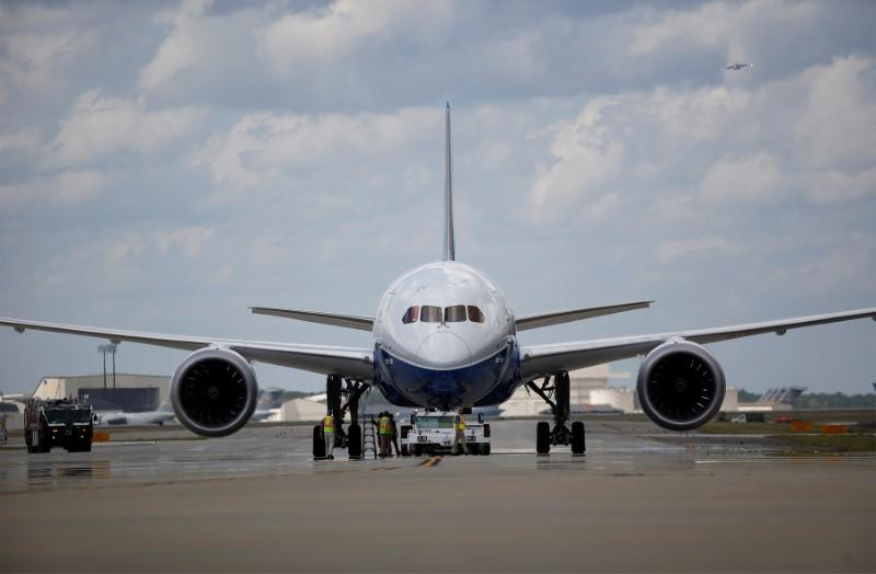 Workers check over the new Boeing 787-10 Dreamliner after it's first test flight at the Charleston International Airport in North Charleston