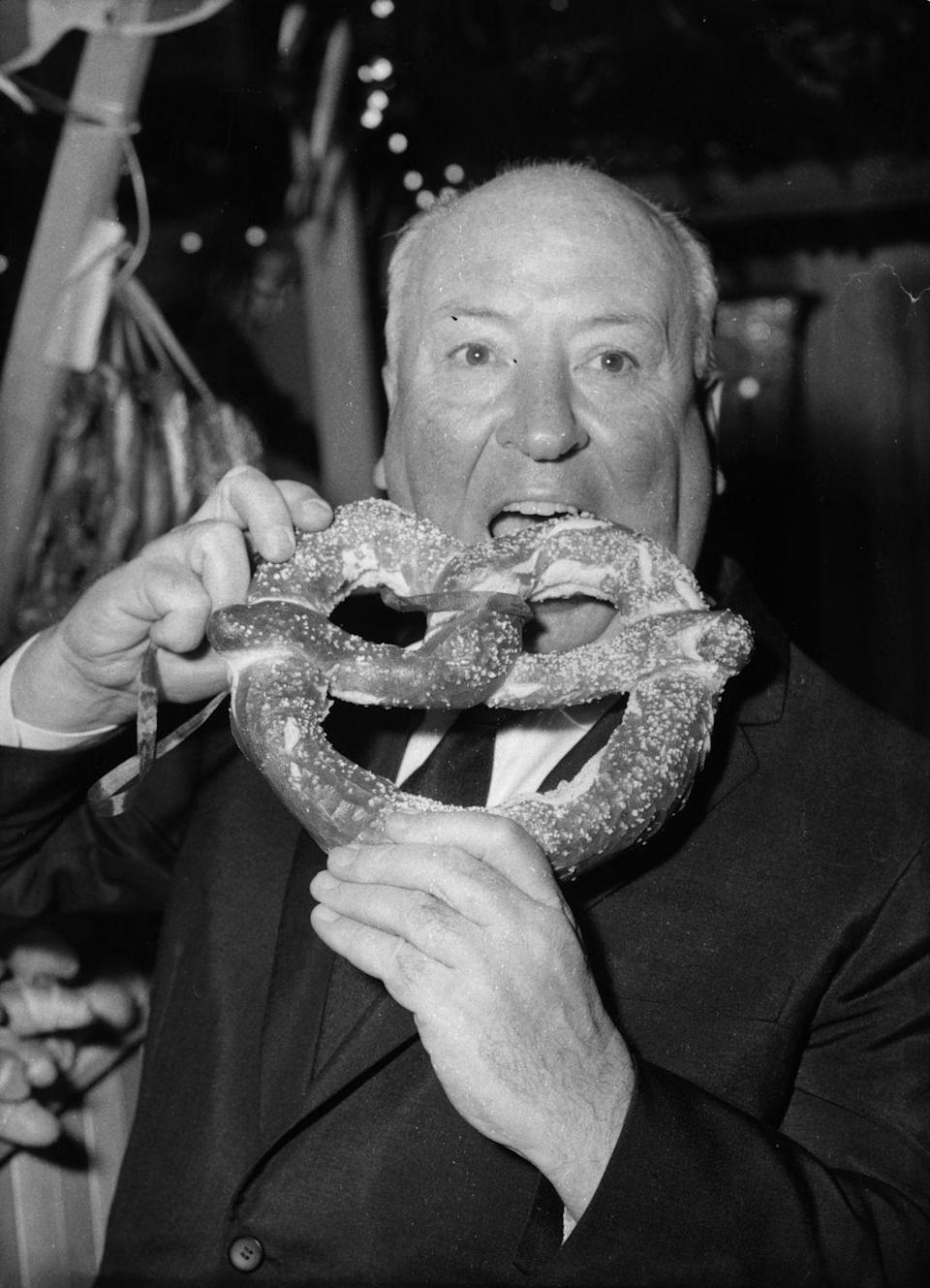<p><em>Psycho</em> director Alfred Hitchcock enjoys a pretzel at the film's premiere on September 28, 1960. The horror/thriller is based on real-life serial killer Ed Gein, who also served as the inspiration for <em>The Texas Chainsaw Massacre</em> and <em>The Silence of the Lambs</em>.</p>