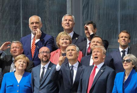 (First row L-R) German Chancellor Angela Merkel, Belgium's Prime Minister Charles Michel, NATO Secretary General Jens Stoltenberg, US President Donald Trump, Britain's Prime Minister Theresa May (second row L-R) Denmark's Prime Minister Lars Lokke Rasmussen, Norway's Prime Minister Erna Solberg, Poland's President Andrzej Duda, French President Emmanuel Macron (third row) Albania's Prime Minister Edi Rama, Czech Republic President Milos Zeman and Spain's Prime Minister Pedro Sanchez pose for a family picture ahead of the opening ceremony of the NATO (North Atlantic Treaty Organization) summit, at the NATO headquarters in Brussels, Belgium July 11, 2018. Ludovic Marin/Pool via REUTERS