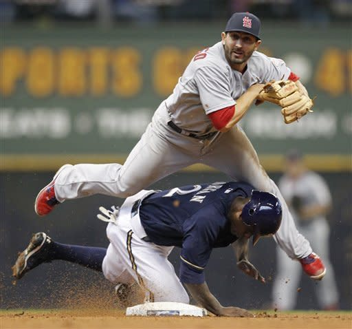 St. Louis Cardinals' Daniel Descalso, top, forces out Milwaukee Brewers' Nyjer Morgan and throws on to first base to complete a double play on Brewers' Ryan Braun during the sixth inning of a baseball game, Saturday, April 7, 2012, in Milwaukee. (AP Photo/Jeffrey Phelps)