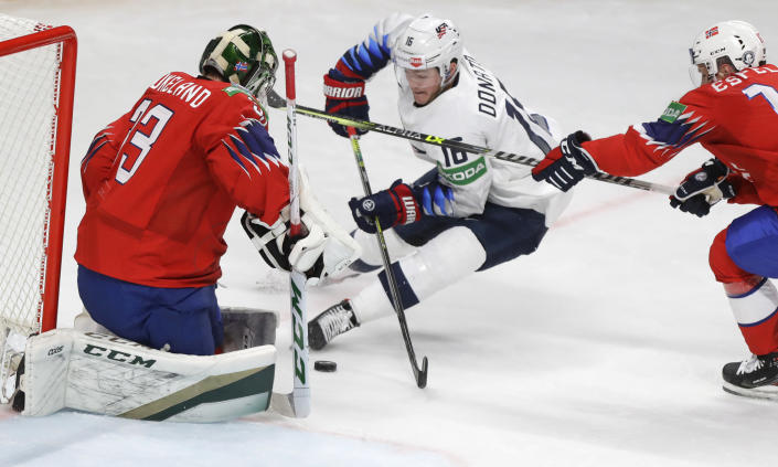 Ryan Donato of the US, centre, challenges for the puck with Norway's goaltender Henrik Haukeland, left, and Norway's Stefan Espeland during the Ice Hockey World Championship group B match between Norway and United States at the Arena in Riga, Latvia, Saturday, May 29, 2021. (AP Photo/Sergei Grits)