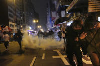 Protesters react as police fire tear gas during a demonstration in Hong Kong, early Wednesday, Jan. 1, 2020. Chinese President Xi Jinping in a New Year's address Tuesday has called for Hong Kong to return to stability following months of pro-democracy protests that began in June over a proposed extradition law, and have spread to include other grievances and demands for more democracy. (AP Photo/Vincent Yu)
