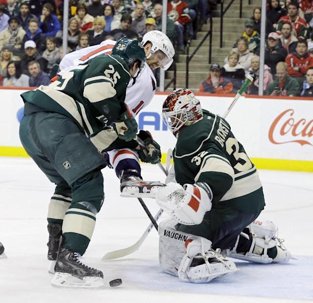 Minnesota Wild goalie Niklas Backstrom, right, of Finland, deflects a shot by Washington Capitals right wing Eric Fehr, center, as Wild defenseman Jonas Brodin (25) defends during the second period of an NHL hockey game in St. Paul, Minn., Saturday, Jan. 4, 2014. (AP Photo/Ann Heisenfelt)