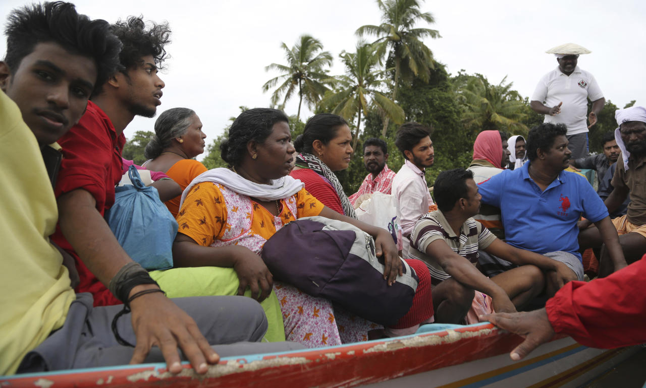 People travel in boat after they were rescued from a flooded area in Chengannur in the southern state of Kerala, India, Sunday, Aug.19, 2018. Some 800,000 people have been displaced and over 350 have died in the worst flooding in a century. (AP Photo/Aijaz Rahi)