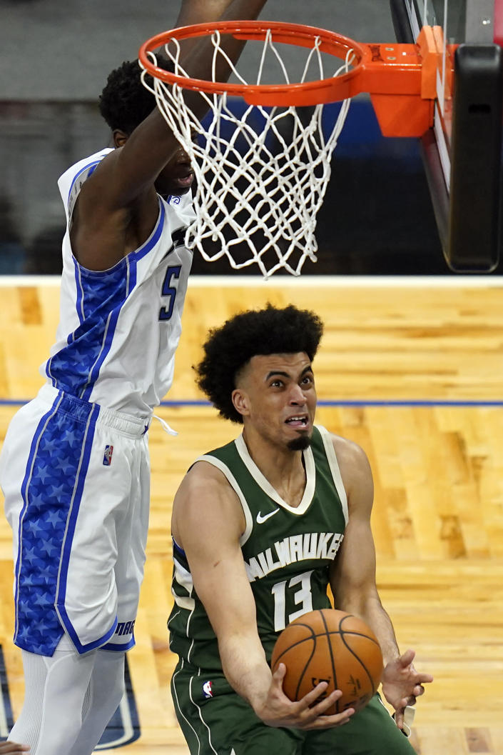 Milwaukee Bucks forward Jordan Nwora, right, goes past Orlando Magic center Mo Bamba, left, for a shot during the second half of an NBA basketball game, Sunday, April 11, 2021, in Orlando, Fla. (AP Photo/John Raoux)