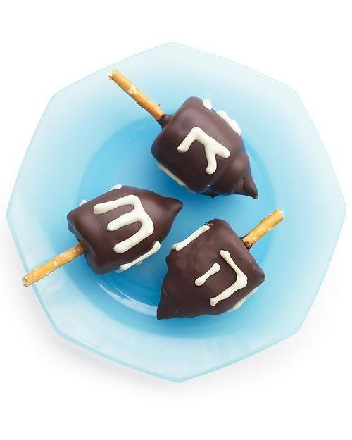 """<p>These fun, kid-friendly treats are a simple spin on the Hanukkah top. Marshmallows form the dreidels' bodies, chocolate kisses serve as the tips, and pretzel sticks stand in for knobs. <a href=""""https://www.yahoo.com/food/good-things-three-tasty-treats-for-hanukkah-104705403785.html"""" data-ylk=""""slk:Get the recipe here.;outcm:mb_qualified_link;_E:mb_qualified_link;ct:story;"""" class=""""link rapid-noclick-resp yahoo-link"""">Get the recipe here.</a><i> (Photo: Martha Stewart)</i><br></p>"""