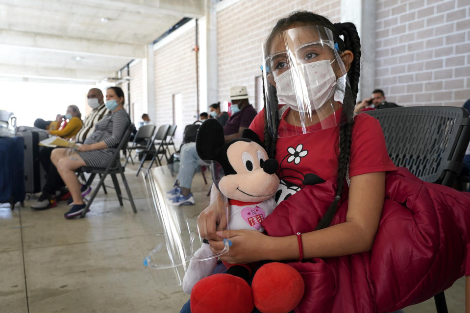 Genesis Cuellar, 8, a migrant from El Salvador, sits in a waiting area to be processed by Team Brownsville, a humanitarian group, helping migrants released from U.S. Customs and Border Protection custody, Wednesday, March 17, 2021, in Brownsville, Texas. The group will facilitate travel so that Cuellar, who is traveling with her mother, Ana Icela Cuellar, can be reunited with her her brother, Andy Nathanael, 4, and their father Marvin Giovani Perez Bonilla, who have been residing in Maryland after being released from custody. The Cuellar family separated in August of 2020, when they tried to cross the U.S.-Mexico border. (AP Photo/Julio Cortez)