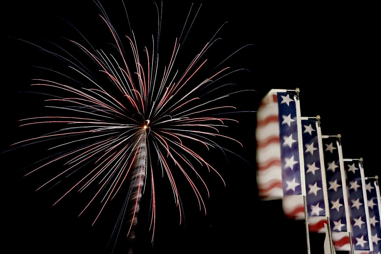 Banners with the United States flag colors wave as fireworks burst in the air during the Fourth of July Independence Day show at State Fair Meadowlands, Tuesday, July 3, 2012, in East Rutherford, N.J. (AP Photo/Julio Cortez)
