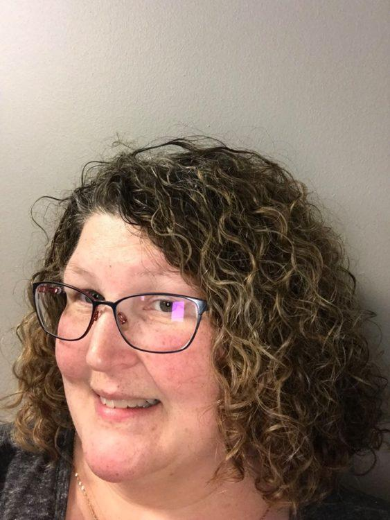 woman with curly hair and glasses smiling