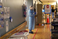 """FILE - In this Jan. 26, 2021, file photo, registered nurse Diane Miller stands in the """"hot zone,"""" defined by red tape on the floor, as she waits to exchange equipment with a colleague who will remain on the other side of the tape in the COVID acute care unit at UW Medical Center-Montlake in Seattle. Coronavirus hospitalizations are falling across the United States, but deaths have remained stubbornly high. (AP Photo/Elaine Thompson, File)"""