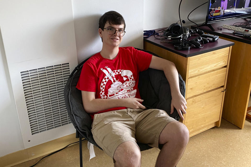 In this Aug. 17, 2020, photo provided by University of Connecticut senior Ryan Bologna, he poses for a photo in his dorm room in Storrs, Conn. Bologna is under indefinite quarantine in his dorm room at Garrigus Suites after several students in that dorm tested positive for coronavirus. (Lisa Bologna/Courtesy of Ryan Bologna via AP)