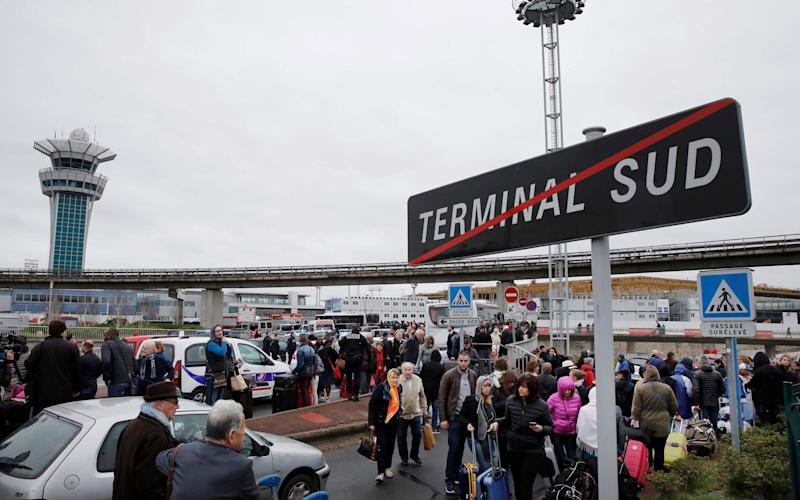 Passengers wait at Orly airport southern terminal after a shooting incident near Paris - Credit: Reuters