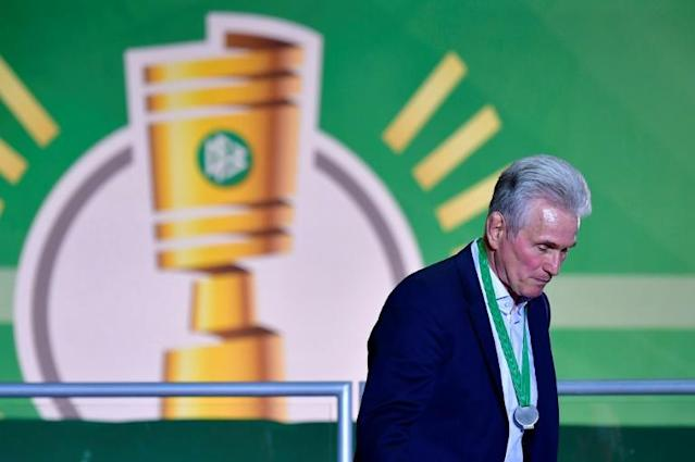 Bayern Munich's German head coach Jupp Heynckes walks with his medal past a logo of the German Cup DFB Pokal after the German Cup DFB Pokal final football match FC Bayern Munich vs Eintracht Frankfurt at the Olympic Stadium in Berlin on May 19, 2018