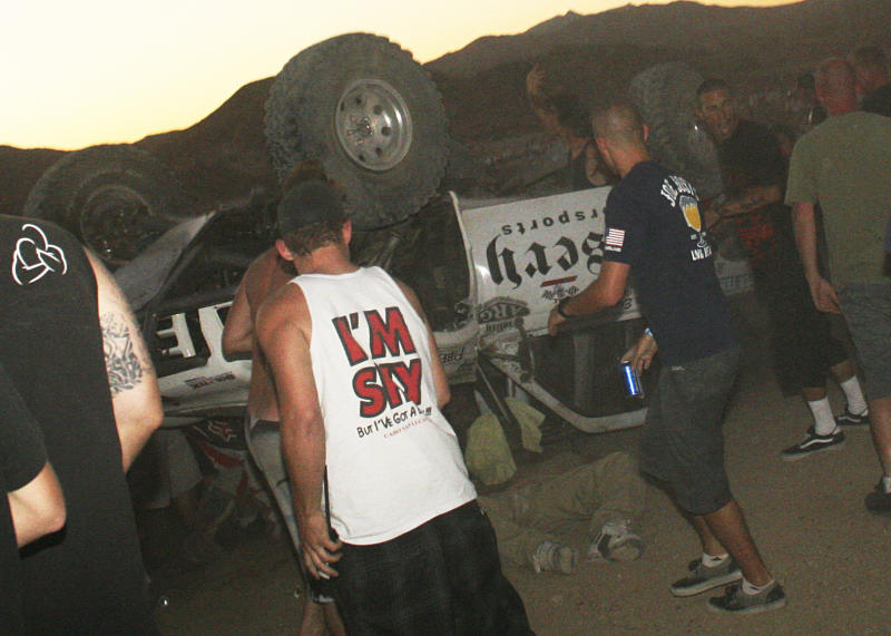 FILE - EDITORS NOTE GRAPHIC CONTENT - In this Aug. 14, 2013 file photo, bystanders rush to help a victim, center, pinned under an overturned off-road race truck moments after it plowed into a crowd after sailing off a jump at the California 200 off-road race in Lucerne Valley Calif. A lawyer said Wednesday, Dec. 18, 2013, that a global settlement has been reached to pay $5.8 million to the families of eight people killed and 12 injured in the California desert off-road race crash. Attorney Katherine Harvey-Lee said an agreement was reached in mediation with federal government lawyers. Harvey-Lee says the agreement still must be approved by the Department of Justice and signed off by a judge. She says she represents three injured spectators and the father of one of those killed. (AP Photo/Dave Conklin, File)