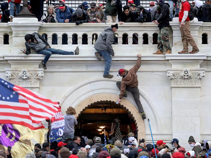 A mob of supporters of President Donald Trump fight with members of law enforcement at a door they broke open as they storm the Capitol Building in Washington on 6 January 2021 (REUTERS)
