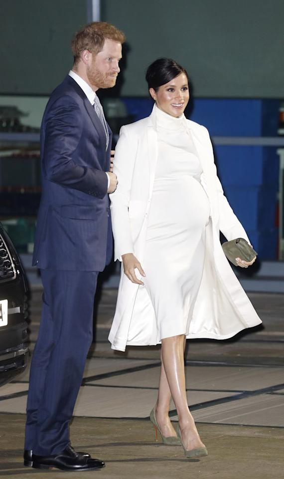 """<p>Meghan is wearing <a rel=""""nofollow"""" href=""""https://www.townandcountrymag.com/style/fashion-trends/a26294017/meghan-markle-white-dress-coat-wider-earth/"""">a white dress by Calvin Klein</a> with an Amanda Wakeley coat.</p>"""