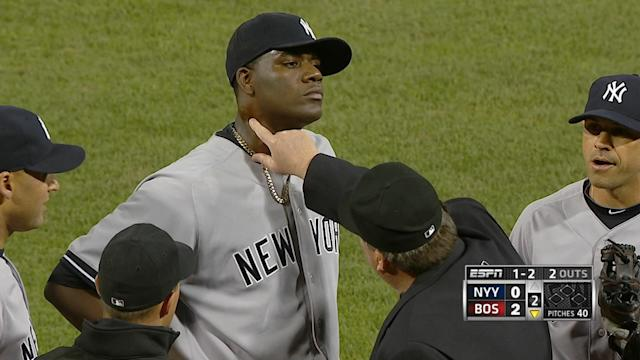 In this April 23, 2014 photo taken from video and provided by ESPN, home plate umpire Gerry Davis touches the neck of New York Yankees starting pitcher Michael Pineda in the second inning of the Yankees' baseball game against the Boston Red Sox at Fenway Park in Boston. Pineda was ejected after umpires found a foreign substance on his neck. (AP Photo/ESPN)