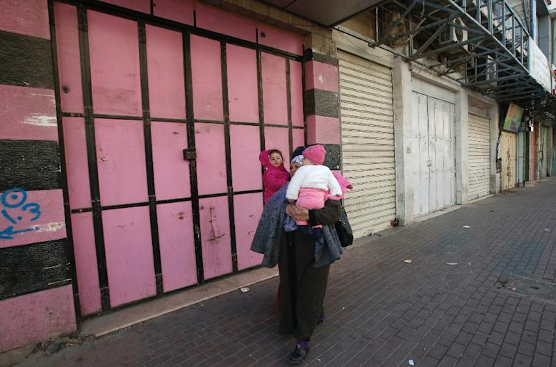 A Palestinian woman carries her children past shuttered shops in the West Bank city of Hebron as thousands strike against plans for a new government-managed social security fund they fear will give them no pensions security (AFP Photo/HAZEM BADER)