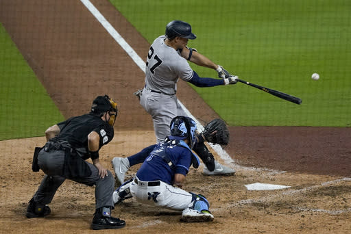 New York Yankees designated hitter Giancarlo Stanton (27) connects for a grand slam home run against the Tampa Bay Rays during the ninth inning in Game one of a baseball American League Division Series Monday, Oct. 5, 2020, in San Diego. (AP Photo/Gregory Bull)