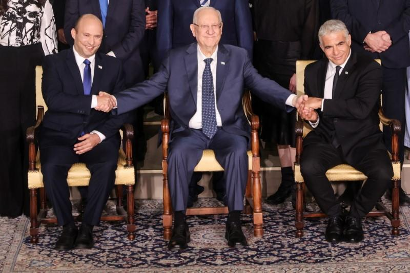 Israel's President Reuven Rivlin between Prime Minister Naftali Bennett and Foreign Minister Yair Lapid as they pose for a group photo with ministers of the new Israeli government