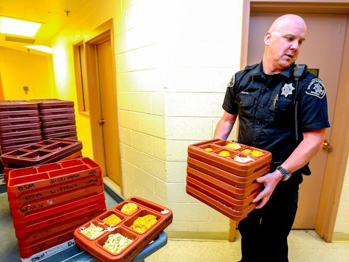 Boulder County Sheriff's Deputy C. Mecca prepares meals for inmates lunch time in the maximum security area at the Boulder County Jail on Monday June 2, 2014. For more photos and video from the jail go to www.dailycamera.com. (Photo by Paul Aiken/Digital First Media/Boulder Daily Camera via Getty Images)
